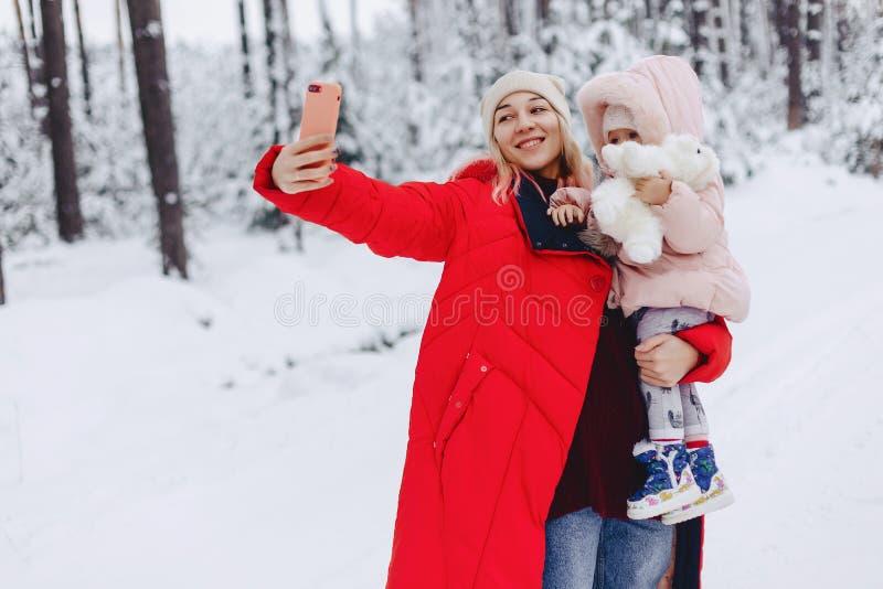 het mamma houdt een kleine dochter die een selfie doen stock afbeeldingen