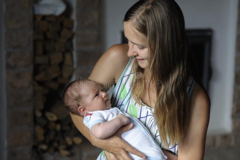 Het mamma koestert haar baby in haar wapens stock foto
