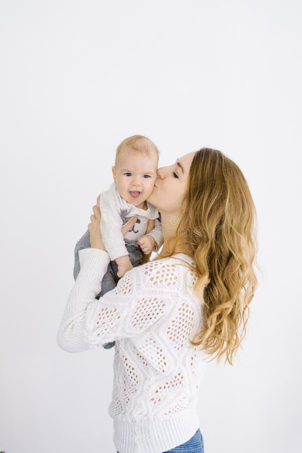 Het mamma kust haar baby op de wang, de kindglimlachen Portret op witte achtergrond De ruimte van het exemplaar Het concept een g stock foto's