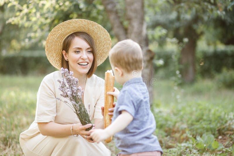 Het mamma met een kind loopt in een paar Zij houdt bloemen en baguette en het kind houdt ook baguette stock foto