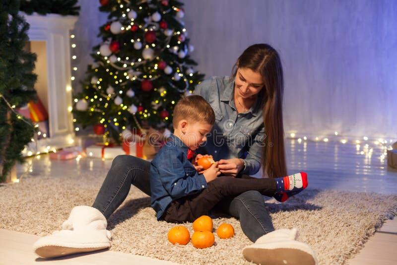 Het mamma met zonen eet de Kerstboomgiften van het mandarijnen nieuwe jaar stock afbeelding