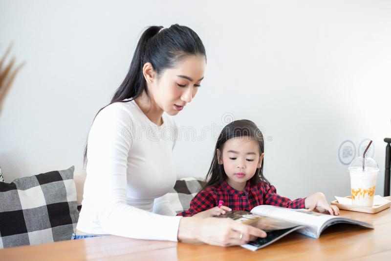 Het mamma onderwijst haar dochter om een boek te lezen royalty-vrije stock afbeelding