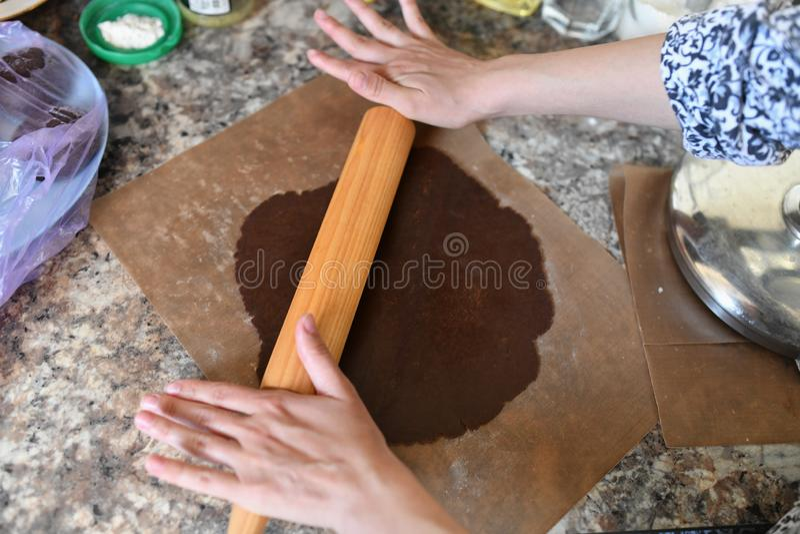 Het mamma rolt deeg Chocoladedeeg Handen die met het receptenbrood van de deegvoorbereiding werken Vrouwelijke handen die deeg vo stock foto
