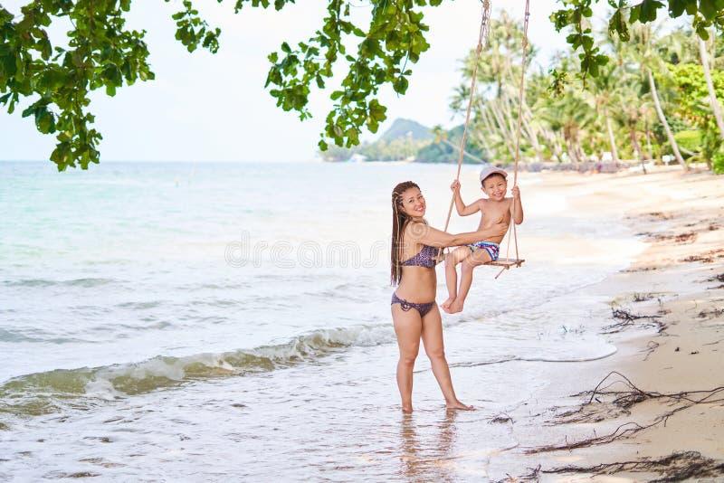 Het mamma rolt haar zoon op een schommeling op de kust van de baai - zandige kust, vage achtergrond stock fotografie