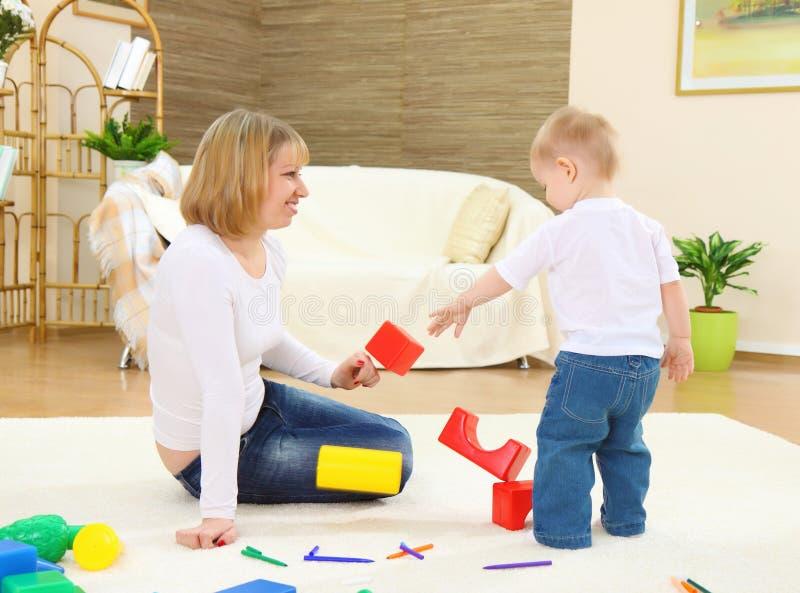Het mamma speelt met kind op een vloer stock foto