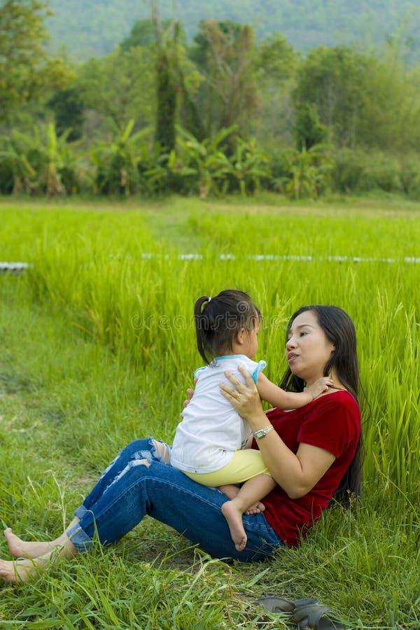 Het mamma van het levensstijlportret en dochter in geluk bij de buitenkant in de weide, Grappige Aziatische familie in een padiev stock fotografie