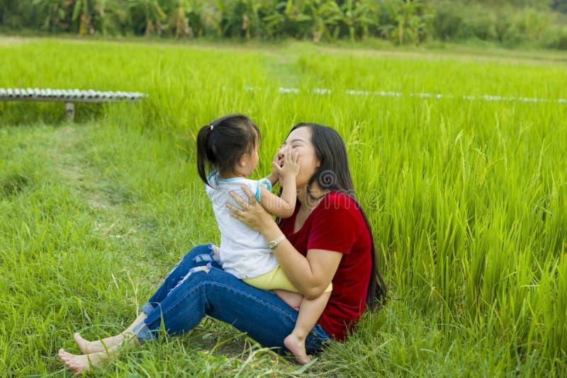Het mamma van het levensstijlportret en dochter in geluk bij de buitenkant in de weide, Grappige Aziatische familie in een padiev stock foto