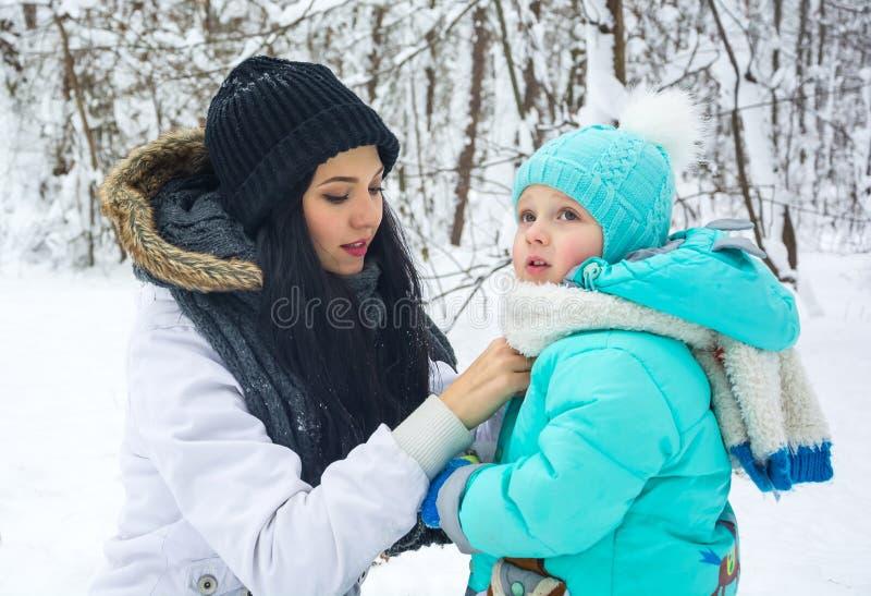 Het mamma verhelpt een kleding aan de kleine zoon in een de winterpark royalty-vrije stock fotografie