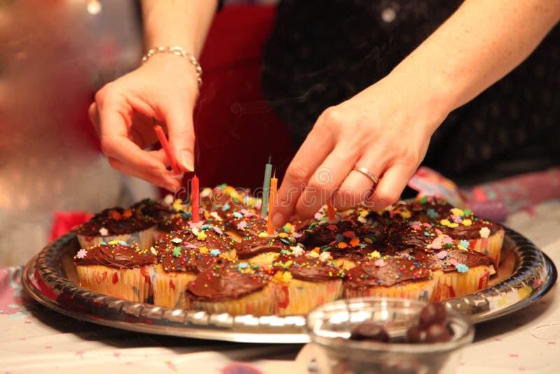 Het mamma verwijdert verjaardagskaarsen uit een partijdienblad van cupcakes stock afbeeldingen