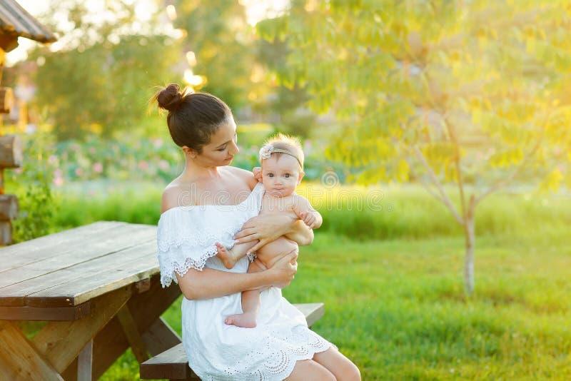 Het mamma verzorgt haar kind in aard Gelukkige familiezitting op de zonsondergangachtergrond stock foto