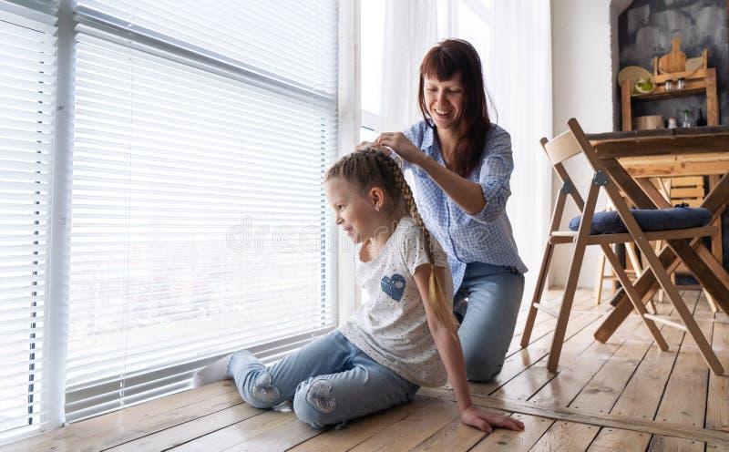 Het mamma vlecht het haar van haar dochter thuis in vlechten dichtbij een groot helder venster stock afbeelding