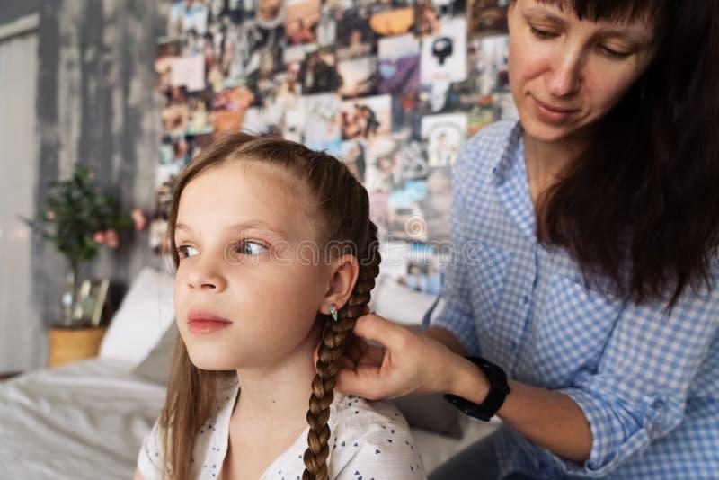 Het mamma vlecht zorgvuldig het haar van haar geliefde dochter in vlechten op haar hoofd stock foto