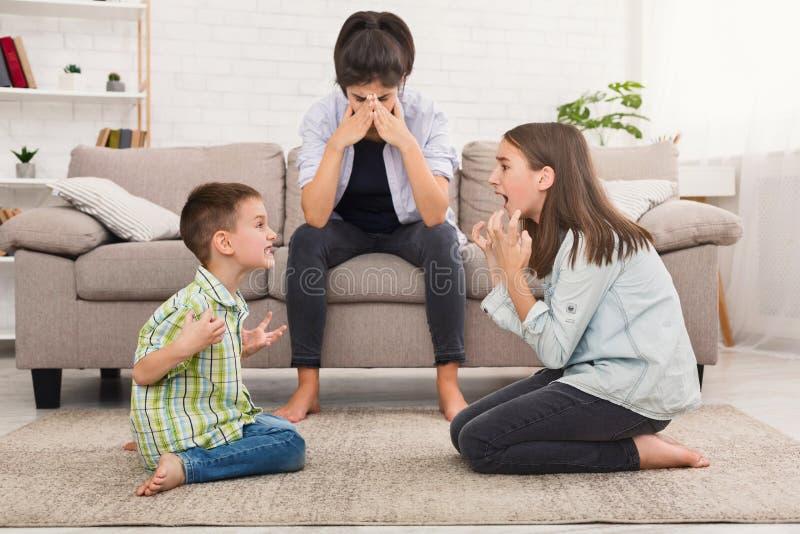 Het mamma wordt ingedrukt door gillende kinderen, siblings die ruzie hebben stock foto's