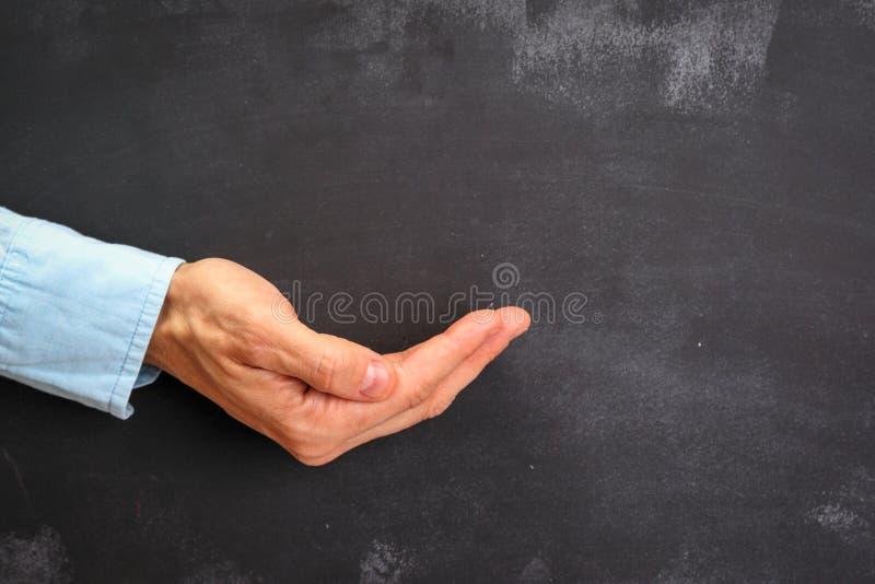 Het Man hand gesturing op donker bord met exemplaar-ruimte stock foto