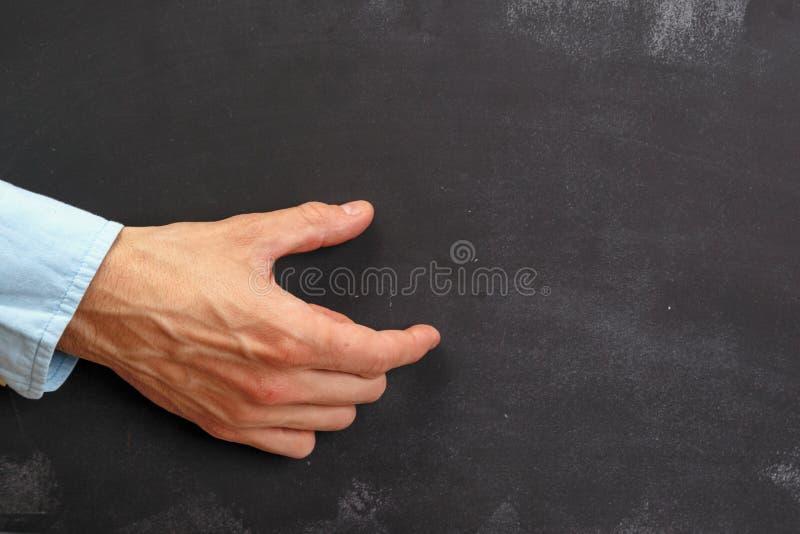 Het Man hand gesturing op donker bord met exemplaar-ruimte stock fotografie