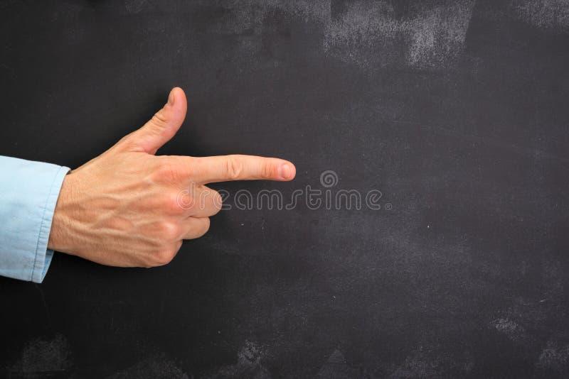 Het Man hand gesturing op donker bord met exemplaar-ruimte stock foto's