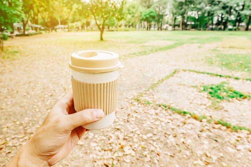 Het man handen houden haalt document koffiekop met ochtend hete drank met weg het inspireren van mening over abstracte parkachter royalty-vrije stock afbeelding