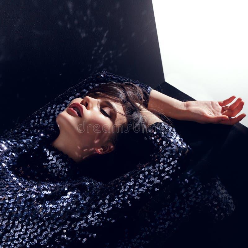 Het manierconcept, schitterend model, met gesloten ogen in lovertjes kleedt het stellen in studio, die op een zwarte achtergrond  royalty-vrije stock afbeeldingen