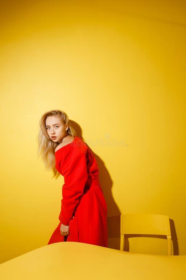 Het maniermeisje blogger gekleed in modieuze rode laag bevindt zich door de gele lijst aangaande de achtergrond van gele muren stock afbeeldingen