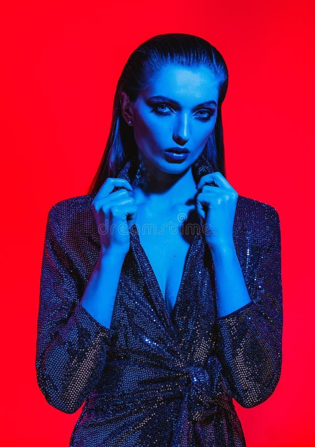 Het maniermeisje met lang haar en modieuze make-up in een zwarte glanzende kleding stelt op de rode achtergrond in neonlicht in royalty-vrije stock foto