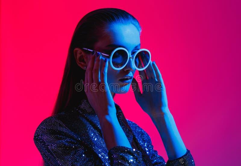 Het maniermeisje met lang haar en ronde zonnebril in een zwarte glanzende kleding stelt in neonlicht in de studio stock foto's