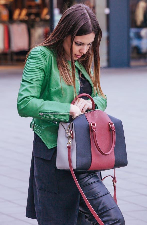 Het maniermeisje op straat zoekt iets in haar handtas stock foto
