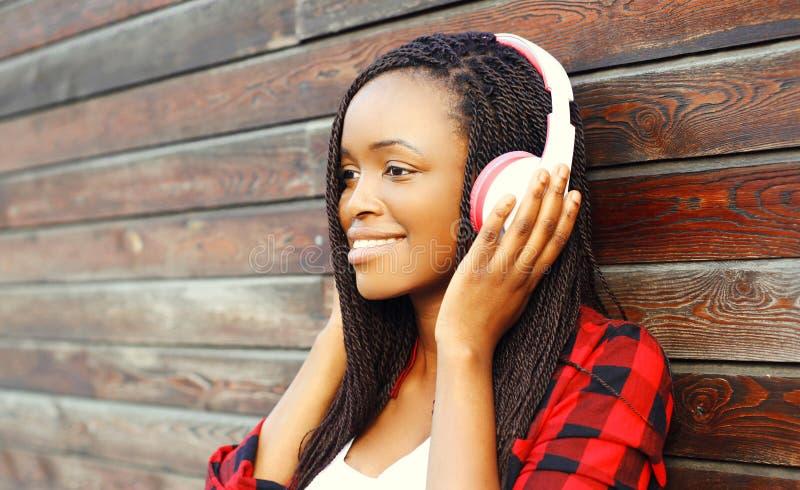 Het manierportret de gelukkige glimlachende Afrikaanse vrouw met hoofdtelefoons geniet van luistert aan muziek over achtergrond royalty-vrije stock foto's