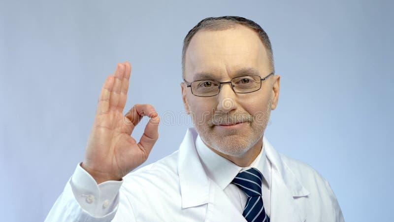 Het mannelijke arts glimlachen, die O.K. gebaar, zeker van succesvolle behandeling tonen vloeit voort royalty-vrije stock afbeeldingen