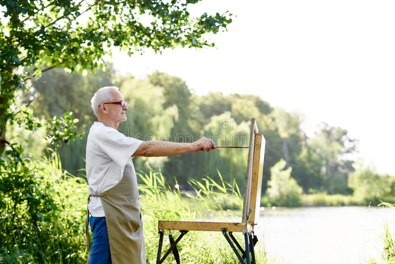Het mannelijke beeld van de schilderstekening bij dag bij park tegen meer stock afbeelding