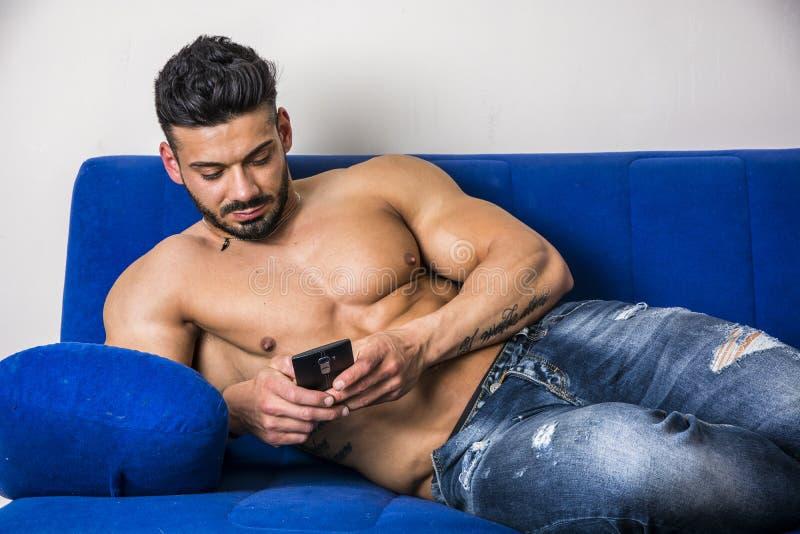 Het mannelijke bodybuilder typen op cellphone op bank royalty-vrije stock afbeeldingen