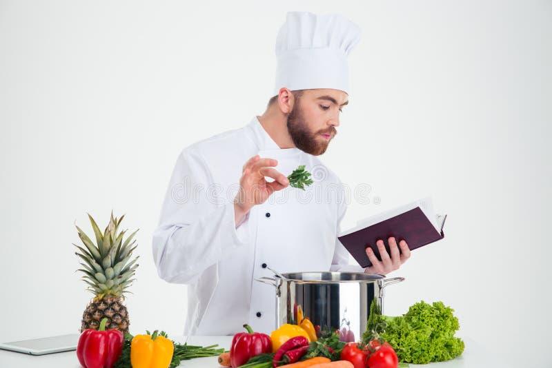 Het mannelijke boek van het de lezingsrecept van de chef-kokkok terwijl het voorbereiden van voedsel royalty-vrije stock foto