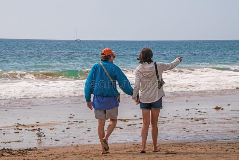 Het mannelijke en vrouwelijke Kaukasische paar die van de bejaardebaby boomer op het strand naar de het oceaanholding handen en r stock fotografie
