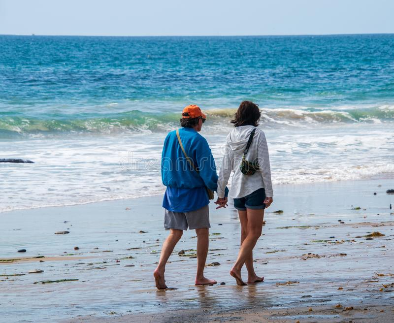 Het mannelijke en vrouwelijke Kaukasische paar die van de bejaardebaby boomer op het strand naar de oceaanholdingshanden lopen royalty-vrije stock afbeelding
