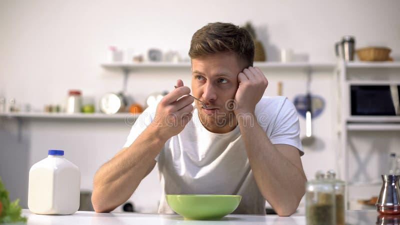 Het mannelijke eten ontbijten en het denken over het werk, het gemakkelijke begin van de maaltijddag, voedsel royalty-vrije stock afbeeldingen