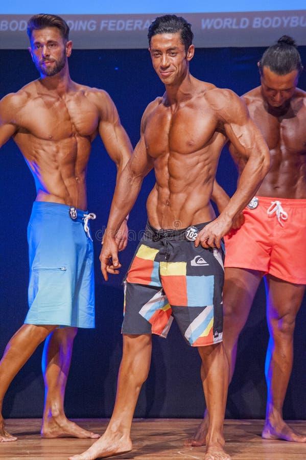 Het mannelijke geschiktheidsmodel toont zijn lichaamsbouw in zwempakom stadium royalty-vrije stock fotografie