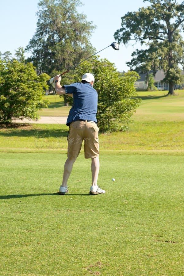 Het mannelijke golfspeler teeing weg met bestuurder royalty-vrije stock foto