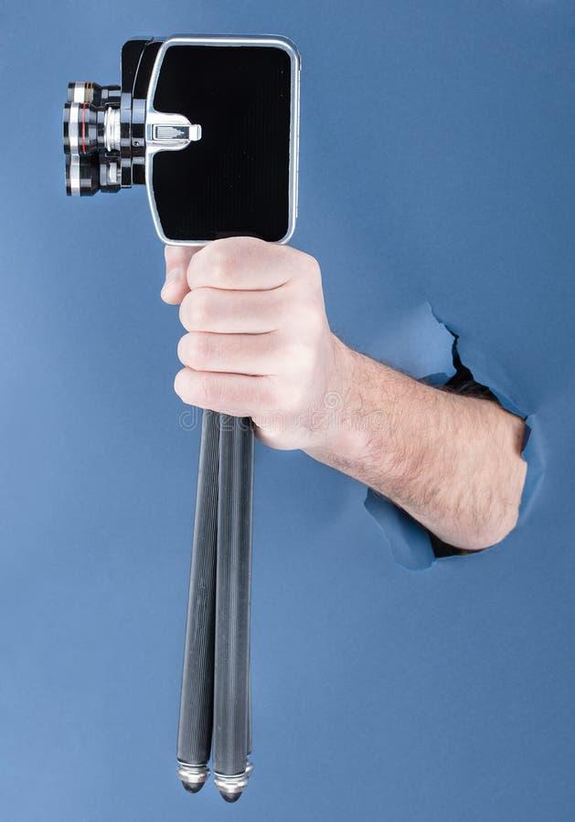 Het mannelijke hand breken door de blauwe document achtergrond en het houden van retro camera stock afbeeldingen