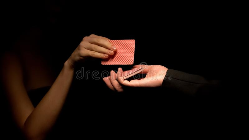 Het mannelijke holdingsdek, vrouw die kaart, illusionist kiezen toont, magische truc dichte omhooggaand royalty-vrije stock afbeeldingen