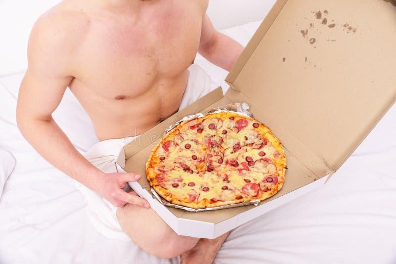 Het mannelijke koeriers sexy spiertorso houdt pizza De sexy koerier levert gastronomische tevredenheid aan uw bed Naakte kerel stock afbeelding