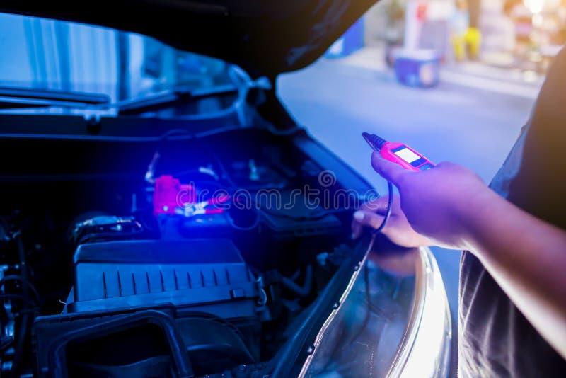 Het mannelijke mechanische meetapparaat van de holdingsbatterij na veranderende autobatterij royalty-vrije stock foto