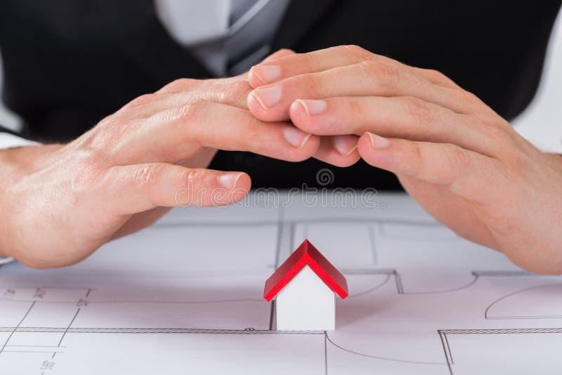 Het mannelijke Model van Architectenhand sheltering house stock foto
