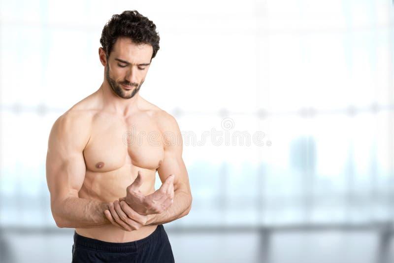 Het mannelijke pak van het holdingsijs op pols las vlek die op plaats van de pijn wijzen stock foto's