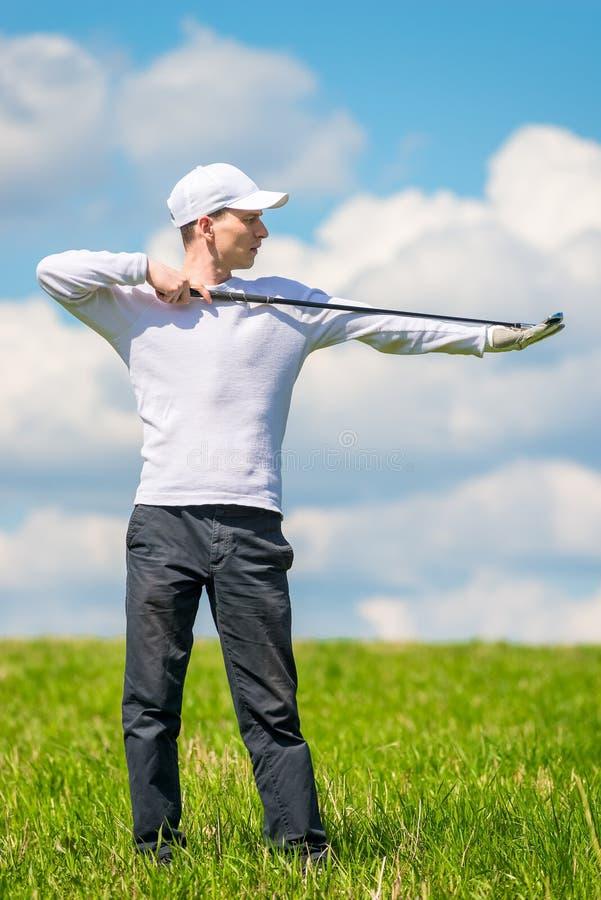 Het mannelijke professionele golfspeler stellen met een golfclub op een groen gebied royalty-vrije stock fotografie