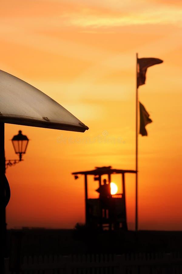 Het Mannelijke Silhouet van Marine Lifeguard Tower With Black op Zonsondergangrug stock foto's