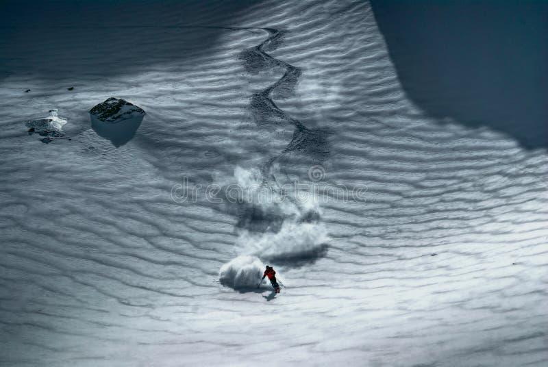 Het mannelijke skiër berijden onderaan de heuvel stock foto's