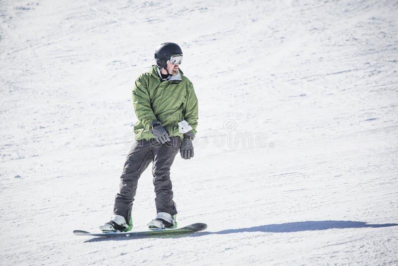 Het mannelijke volwassen snowboarder berijden onderaan een verzorgde sneeuwheuvel royalty-vrije stock afbeelding
