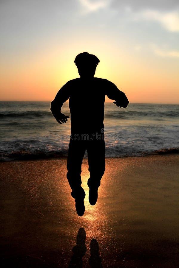 Het mannelijke volwassen springen van het silhouet bij een strand stock afbeeldingen
