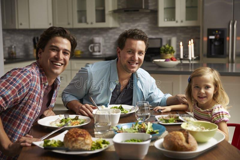 Het mannelijke vrolijke paar en de dochter die thuis kijken aan camera dineren royalty-vrije stock foto's