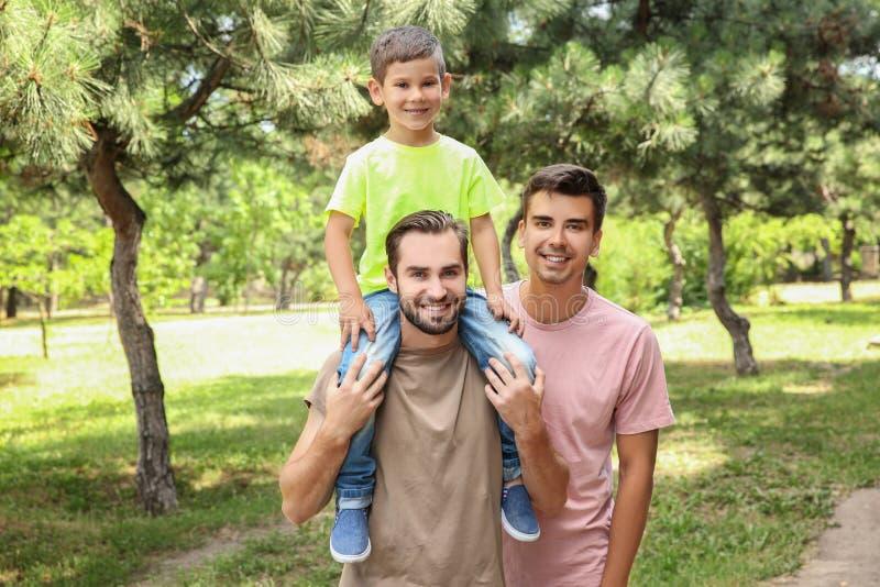 Het mannelijke vrolijke paar met bevordert zoon die pret in park hebben royalty-vrije stock foto