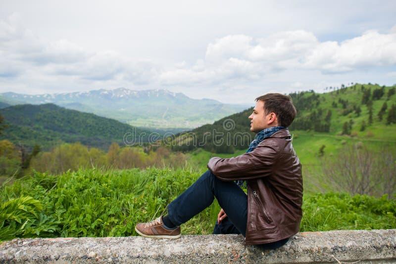 Het mannelijke wandelaar ontspannen bovenop een berg stock afbeelding